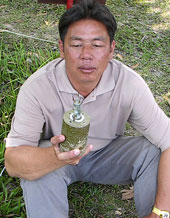 Lim holding a landmine - part of the WRF and McMahan AA efforts to clean up Cambodia